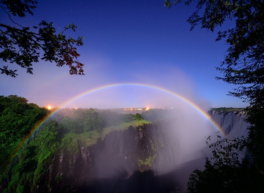 Victoria Falls at night with rainbow and moon